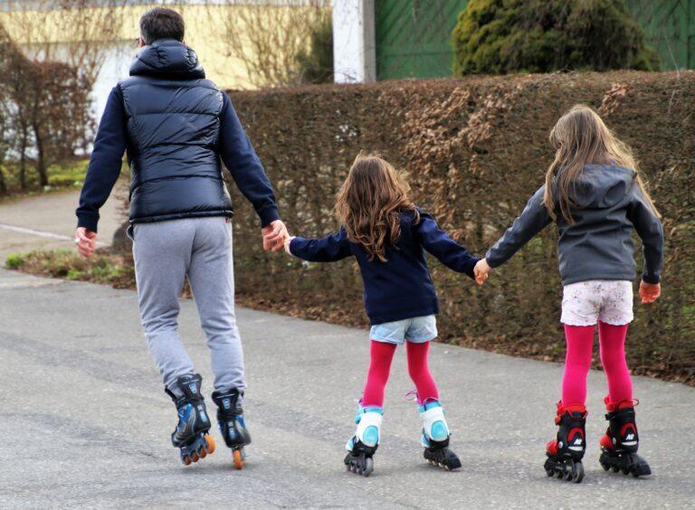 Mann und zwei Mädchen nehmen sich an den Händen und fahren Rollerskates (Rückenansicht)